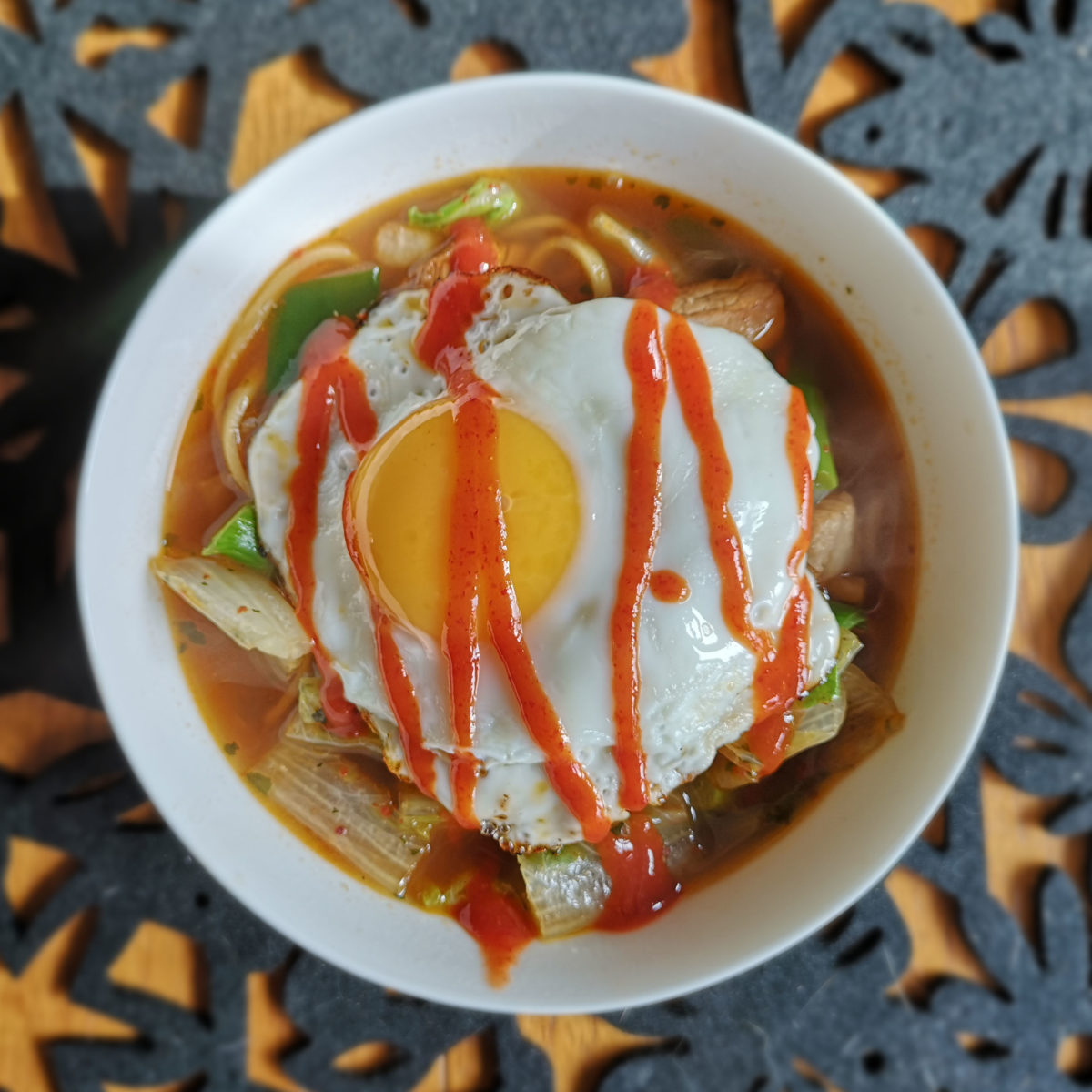 A deep bowl of noodle soup topped with a fried egg